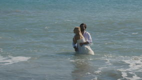 Newlyweds have fun in the ocean. A man brings a woman into the water. Portrait of the groom holds his bride in his arms. Young people laugh and smile. A man is stock video footage