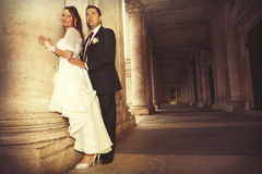 Newlyweds in the historic center of Rome. Ancient columns. Stock Photos