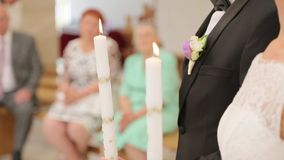 Newlyweds hold candles in the church. Newlyweds hold candles at the wedding in the church stock video