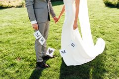 Newlyweds hold hands and hold a paper garland stock image