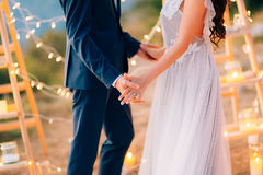 The newlyweds hold hands at the wedding ceremony. Couple holding Stock Photos