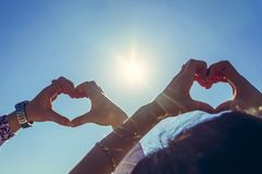 Newlyweds hold their hands in the shape of a heart on the backgr stock images