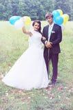 Newlyweds holding balls Royalty Free Stock Image