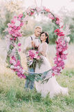 Newlyweds are holding the bouquet of peonies and standing behind the wedding peonies arch in the sunny spring field. Close-up vertical photo Royalty Free Stock Photos