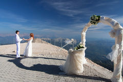 Newlywed couple by white arch. Newlywed couple holding hands on pier by white wedding arch Royalty Free Stock Photo