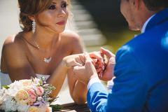 Newlyweds Holding Hands at Table. With bouquet Royalty Free Stock Image