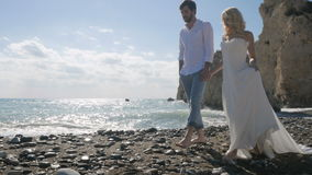 Newlyweds are holding hands and walking on the beach of the ocean stock video footage