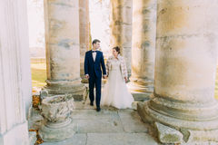 The newlyweds are holding hands while walking among columns of the old church. Royalty Free Stock Image