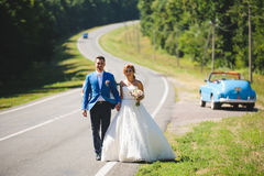 Newlyweds Holding Hands. And walking on road Stock Photos