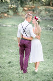 Newlyweds hug each other waists while walking in the grass Royalty Free Stock Photo