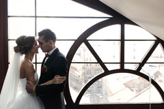 Newlyweds hug in the front of panoramic window Stock Photos