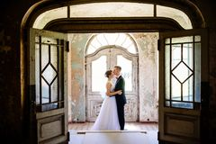 Newlyweds hugging at the door in an old house royalty free stock images