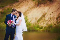 Newlyweds are hugging near the lake Stock Photos