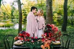 Newlyweds hugging under the plaid next to the festive table. Bride and groom in the park. Autumn wedding. Artwork Stock Photos