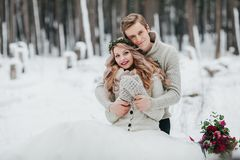 Newlyweds are hugging in the winter forest. Couple in love. Winter wedding ceremony. Artwork Stock Images