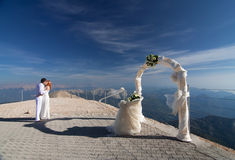 The newlyweds kiss near the wedding arch. And altar against the blue sky Royalty Free Stock Photo
