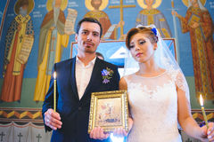 Newlyweds with Icon and Candles Royalty Free Stock Photo