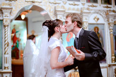 Newlyweds kiss. The bride and groom kiss at the ceremony in the church royalty free stock images