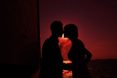 Newlyweds kiss against the setting sun Royalty Free Stock Photo