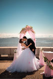Newlyweds kiss near coastline Royalty Free Stock Photography