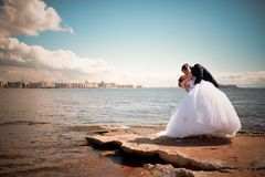 Newlyweds kiss near coastline Stock Photography