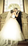 Newlyweds kiss in wedding palace Stock Image