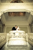 Newlyweds kiss in wedding palace Stock Photography