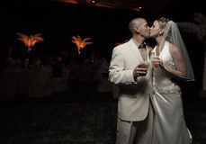 Newlyweds kissing with drinks in hand Royalty Free Stock Photo