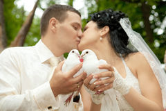 Newlyweds  kissing holding white doves Stock Photos