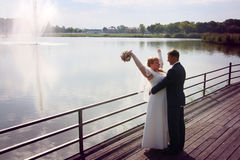 Newlyweds kissing on a jetty at sunset Royalty Free Stock Images
