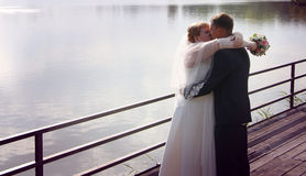 Newlyweds kissing on a jetty at sunset Stock Photo