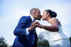 Newlyweds kissing while showing wedding rings stock images