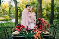 Newlyweds kissing under the plaid next to the festive table. Bride and groom in the park. Autumn wedding. Artwork. Selective focus on couple royalty free stock photo