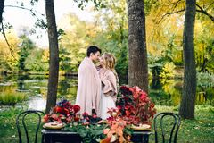 Free Newlyweds Kissing Under The Plaid Next To The Festive Table. Bride And Groom In The Park. Autumn Wedding. Artwork Royalty Free Stock Photography - 102951087