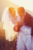 Newlyweds laugh somewhere on the field in the evening. A Stock Images