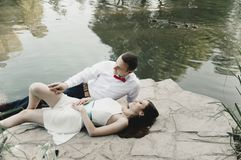 Newlyweds lie on stone near lake with ducks royalty free stock photography