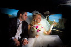Newlyweds in the limo Royalty Free Stock Images