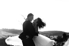 Newlyweds look at each other with love while whirling somewhere. On the field a royalty free stock images