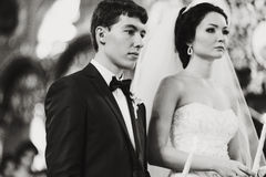 Newlyweds look musing during a ceremony in the church. A royalty free stock photo