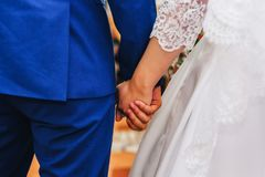 Newlyweds in love bride and groom holding hands together at wedding ceremony. Newlyweds in love bride and groom holding hands together at the wedding ceremony Stock Images