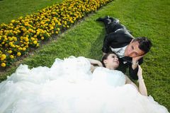Newlyweds lying down on lawn with flowers Stock Photos