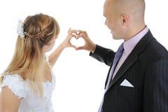 Newlyweds make heart fingers Royalty Free Stock Photos