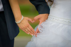 Newlyweds make heart hands Royalty Free Stock Images