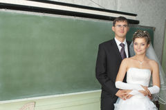 Newlyweds near school blackboard Royalty Free Stock Photos