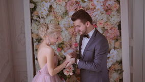 Newlyweds pert smile and rejoice in his happiness. The bride and groom exchange rings at a wedding ceremony in the studio on a background of beautiful flowers stock footage