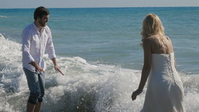 Newlyweds play and have fun in the ocean. Newlyweds play and have fun in the water. The girl leans over to the water and starts to spray. The wave washes people stock video