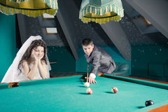 Newlyweds playing billiards Royalty Free Stock Images