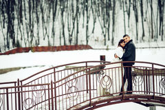 Newlyweds pose on the bridge across a covered with snow lake Stock Photos