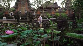Newlyweds posing near buddhist temple in Bali. Holding hands, hugging. Romantic wedding. Tropical vacation stock video