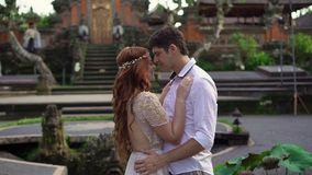 Newlyweds posing near buddhist temple in Bali. Holding hands, hugging. Romantic wedding. Tropical vacation stock footage